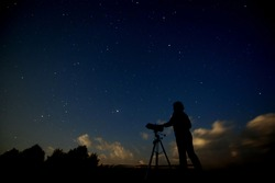 Silhouette of an adult man with a telescope studying the starry sky and galaxies. A man with an astronomical device stands on the background of a natural landscape at night.