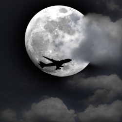 Silhouette of an airplane flying across a full moon at twilight.