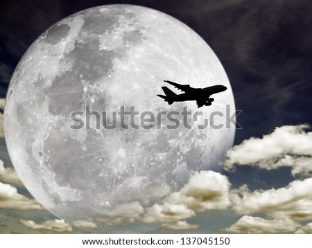 Photo of Silhouette of an airplane flying across a full moon on a cloudy night sky. Elements of this image furnished by NASA.