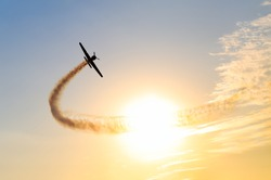Silhouette of an airplane performing acrobatic flight at sundown. Trace of Smoke behind it