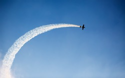 Silhouette of an airplane performing acrobatic flight on blue sky. Trace of Smoke behind