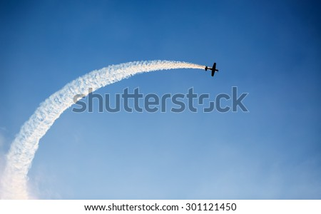 Silhouette of an airplane performing acrobatic flight on blue sky Trace of Smoke behind