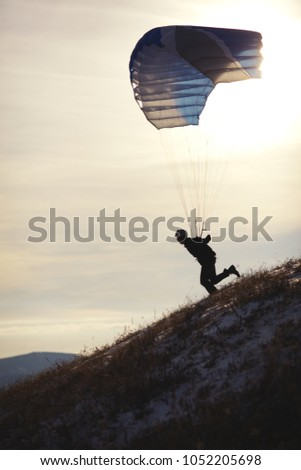 Silhouette of an athlete trying to run up and take off with a parachute filled along the mountainside. Speedflying. #1052205698