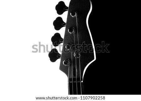 Silhouette of an electric bass guitar on a contrasting black and white background.