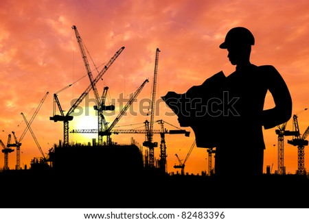 silhouette of an engineer working on construction site at sunset