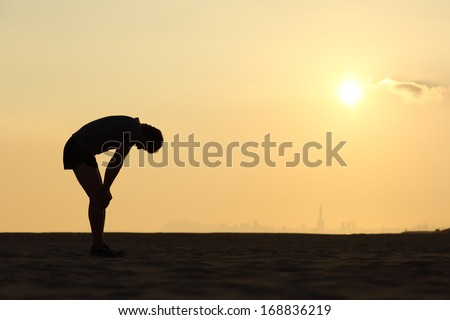 Silhouette of an exhausted sportsman at sunset with the horizon in the background Сток-фото ©