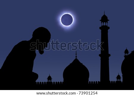 Silhouette of an old muslim praying near a mosque during a total eclipse