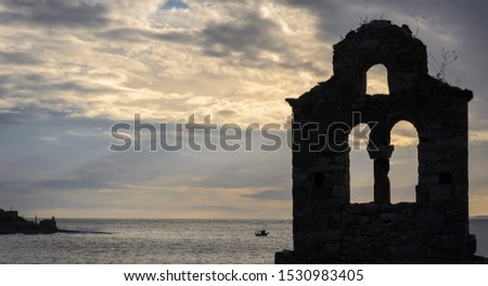 Silhouette of an old stone church with the sea a boat and some sun rays through the clouds in Mani Greece
