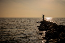 Silhouette of an unknown man standing on the end of a stone pier or small wave shelter in sunset time on a lake or sea.