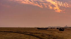 Silhouette of Anchored Boats and people on a beach.