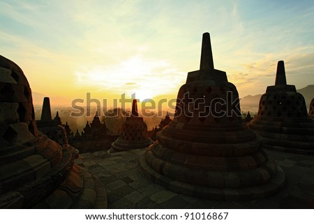 Silhouette of Ancient stupa Borobudur Temple, with sunrise in Yogyakarta, Java, Indonesia.