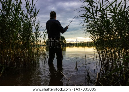 Silhouette of angler catching the fish during sunset