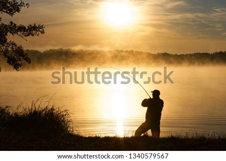 Silhouette of angler during misty sunrise