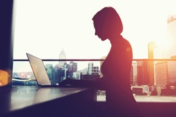 Silhouette of anonymous person using laptop comer and social networks