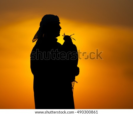 Silhouette of arab man with a falcon on a sunset background. #490300861