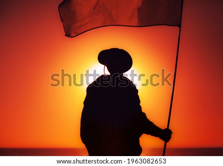 Silhouette of army soldier, commando fighter special forces infantryman standing on background of sunset sky waving on flagpole flag. Military victory, remembrance of fallen soldiers, veterans concept Stock photo ©