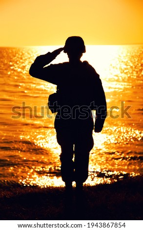 Silhouette of army soldier, Marines fighter in helmet and ammunition saluting while standing on seashore at sunset time. Coast guard fighter, special operations forces soldier honoring fallen comrades Stock photo ©