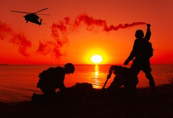 Silhouette of army special forces infantry soldiers, Marines or Navy SEALS team signaling to helicopter with smoke flair while waiting for evacuation, landing on seashore during amphibious operation