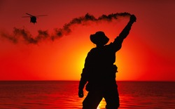Silhouette of army special operations forces soldier, commando fighter signaling, marking landing spot or evacuation area for helicopter pilot with smoke flair while standing on shore during sunset