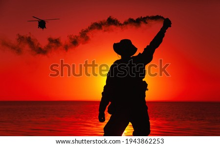 Silhouette of army special operations forces soldier, commando fighter signaling, marking landing spot or evacuation area for helicopter pilot with smoke flair while standing on shore during sunset Stock photo ©