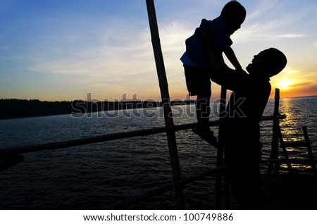 Silhouette of Asian father and son on a bamboo jetty during a bonding moment