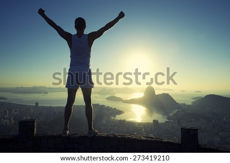 Silhouette of athlete in white sport uniform standing with champion arms raised in front of Rio de Janeiro Brazil sunrise skyline overlook at Sugarloaf Mountain