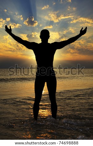 Silhouette of athletic men to the sea at sunset. Give me the power.