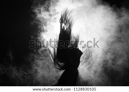 Silhouette of Attractive Body Shape with Fluttering long Hair in Smoke Fog with back light Black Background, Concept of Sport sexy guy girl focus attention on exercise dance fit firm loss weight #1128830105