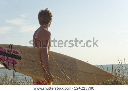 Silhouette of attractive young surfer holding surfboard while standing on dune looking at ocean to find the perfect spot to go surfing waves. Copy space in sky