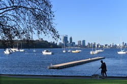 Silhouette of Australian couple walking their dog  in Matilda Bay along the Swan River against Perth financial district  skyline in Western Australia.