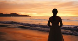 silhouette of back view asian woman standing on the beach during sunset