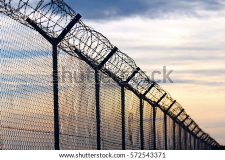 Shutterstock Silhouette of Barbed Wire fence against a Cloudy Sky