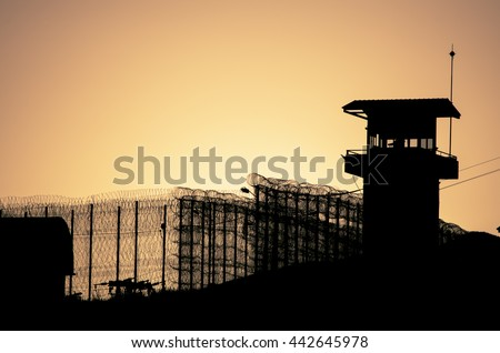 Silhouette of barbed wires and watchtower of prison, at sunset  Foto stock ©