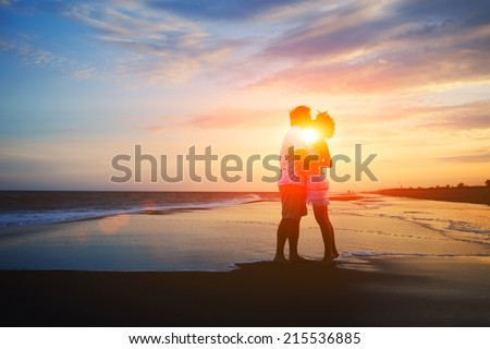 Silhouette of beautiful couple holding hands having romance, valentines day background of couple in love, man and woman kissing on the tropical beach at orange sunset sky, young family at sunset