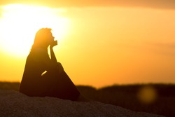 silhouette of beautiful thoughtful girl sitting on the sand and enjoying the sunset, the figure of young woman on the beach, female meditate on nature