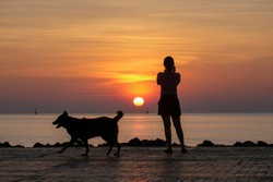 silhouette of beautiful thoughtful girl stand and enjoying the sunset, the figure of young woman on the beach, female meditate on nature