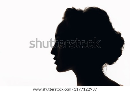 Silhouette of beautiful young woman with a beautiful hairdo. Black and white.