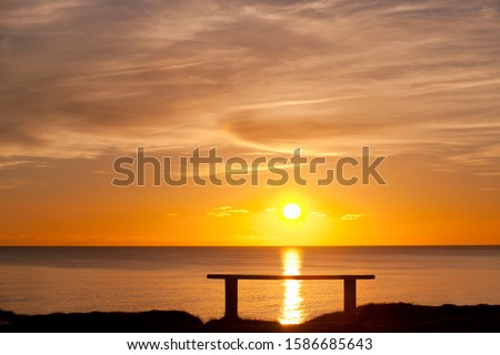 Silhouette of bench with sunset over ocean