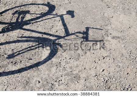 Silhouette of bicycle on cracked asphalt.