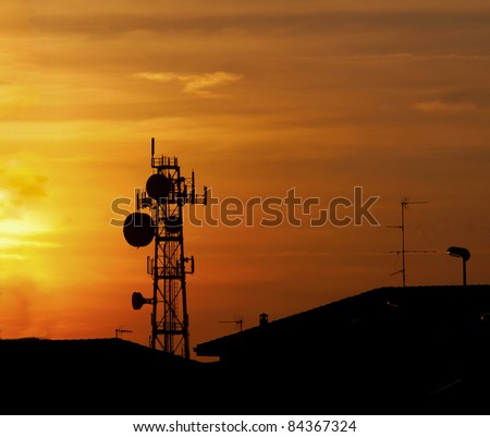 Silhouette of big communication antenna in a woderful orange sunset