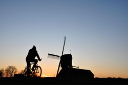 Silhouette of Biker and Dutch windmill during sunset