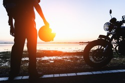 Silhouette of biker and motorcycle with sunrise background, Rider moto trip on the street at the riverside, enjoying freedom and active lifestyle, having fun on a bikers tour
