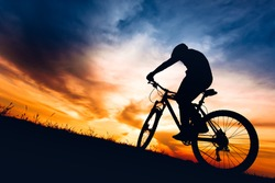 silhouette of biker boy riding mountain bike on hills at sunset
