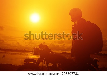Silhouette of biker man  with his motorbike,he shoulder backpack. beside the natural lake and beautiful, enjoying freedom and active lifestyle, having fun on a bikers tour.sunset background and sky.