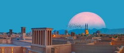 Silhouette of birds flying - Historic City of Yazd with famous wind towers in the background full moon at twilight blue hour - YAZD, IRAN