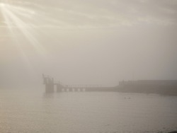 Silhouette of Blackrock public diving tower in a fog. Cloudy sky over ocean with sun beams bursting through clouds. Calm and tranquil atmosphere. Salthill, Galway city, Ireland