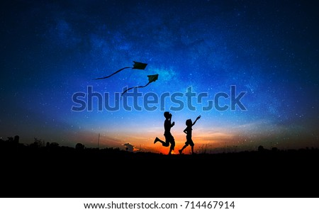Silhouette of boy and girl flying a kite in milky way background. #714467914