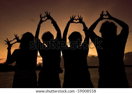 Silhouette of boy and girl forming their hands to heart form