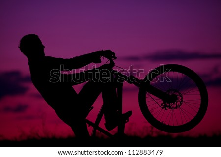 silhouette of boy cyclist in motion on the background of beautiful sunset (dawn)