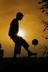 silhouette of boy how plays football in the sunset